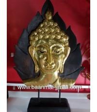 รูปเศียรพระพุทธทองแกะสลักไม้ปิดแผ่นทองคำเปลว ตั้งบนแท่นไม้สีดำ